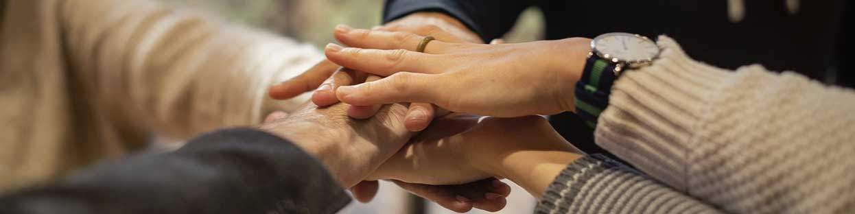 circle of people in treatment stacking their hands together